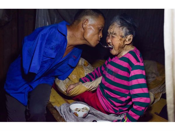 एक किसान बिना हाथों के खिलाता है अपनी मां को खाना