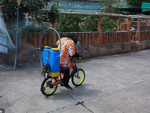 A Making Chimpanzee In A Face Mask Ride A Bicycle While Spraying Coronavirus Sanitizer In Zoo