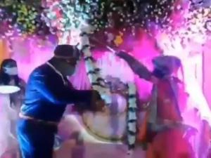 Couple Uses Bamboo Sticks To Exchange Varmalas During Wedding